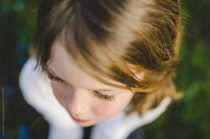 Closeup of girl sitting in grass by Lindsay Crandall for Stocksy United
