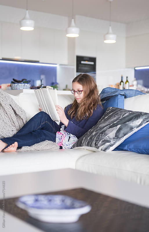 tweens and their electronic devices, girl on sofa indoors by Gillian Vann for Stocksy United