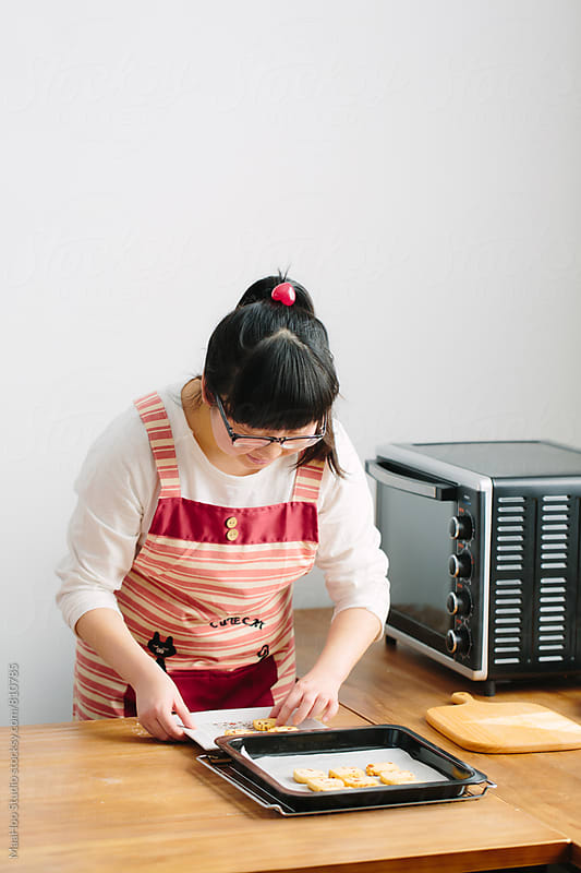 Young Chinese woman baking cookies by MaaHoo Studio for Stocksy United