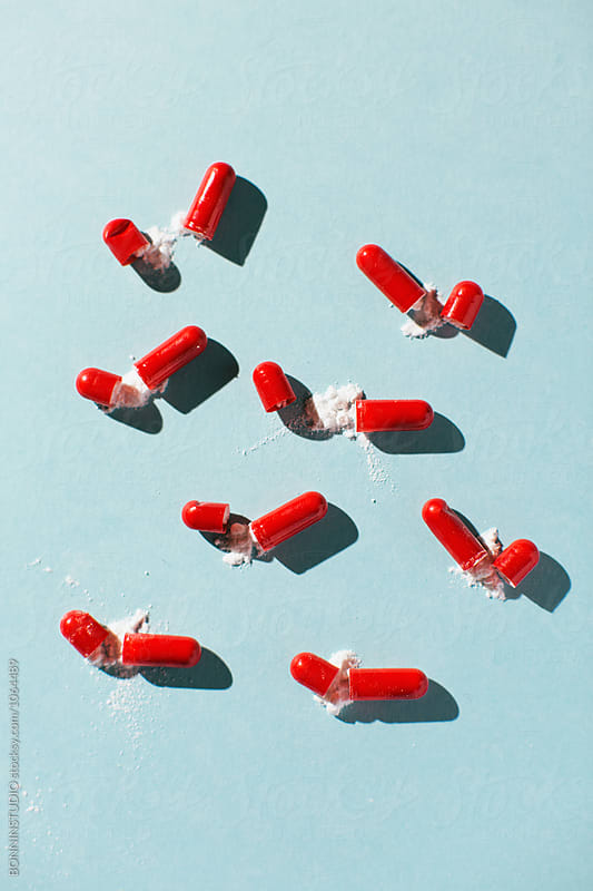 Opened capsules on blue background from above.  by BONNINSTUDIO for Stocksy United