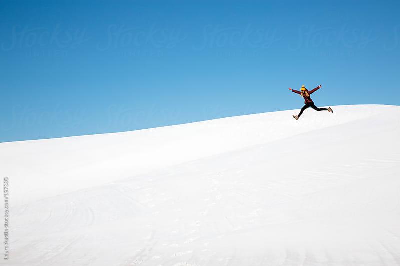 Girl Jumping For Joy On White Sand Dunes by Laura Austin for Stocksy United