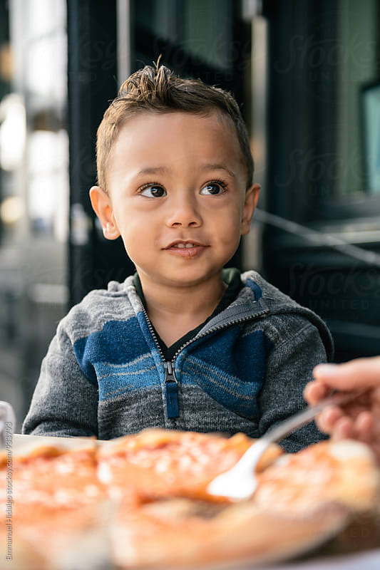 Toddler waiting for his next bite of pizza by Emmanuel Hidalgo for Stocksy United