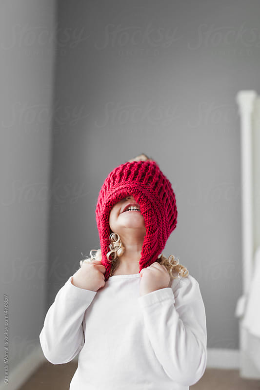Toddler girl struggling to put on red winter hat  by Amanda Worrall for Stocksy United