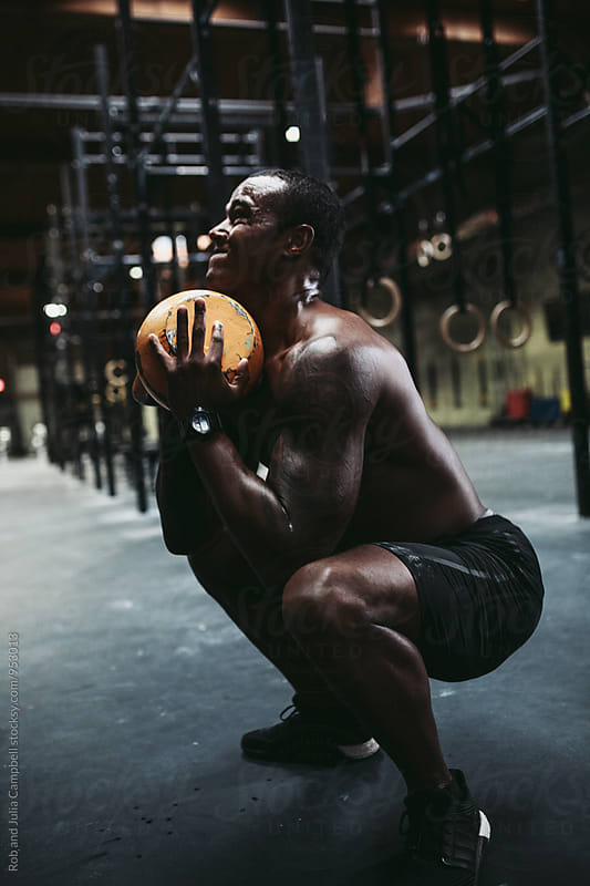 Young, fit black man training hard in fitness gym - lifting kettlebell by Rob and Julia Campbell for Stocksy United