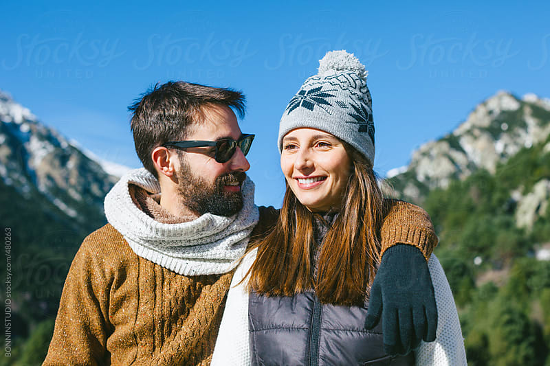 Two lovers enjoying on a sunny winter day at the mountain. by BONNINSTUDIO for Stocksy United