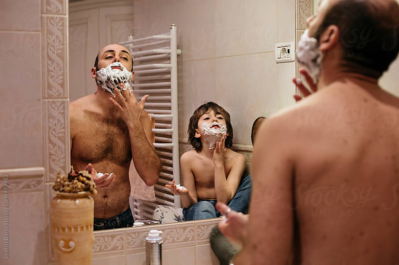 Father and son in front of the mirror distributing shaving foam on the faces by Beatrix Boros for Stocksy United