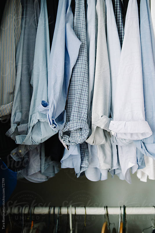 rolled cuffs of long sleeve blue shirts hanging in a man's closet by Tara Romasanta for Stocksy United