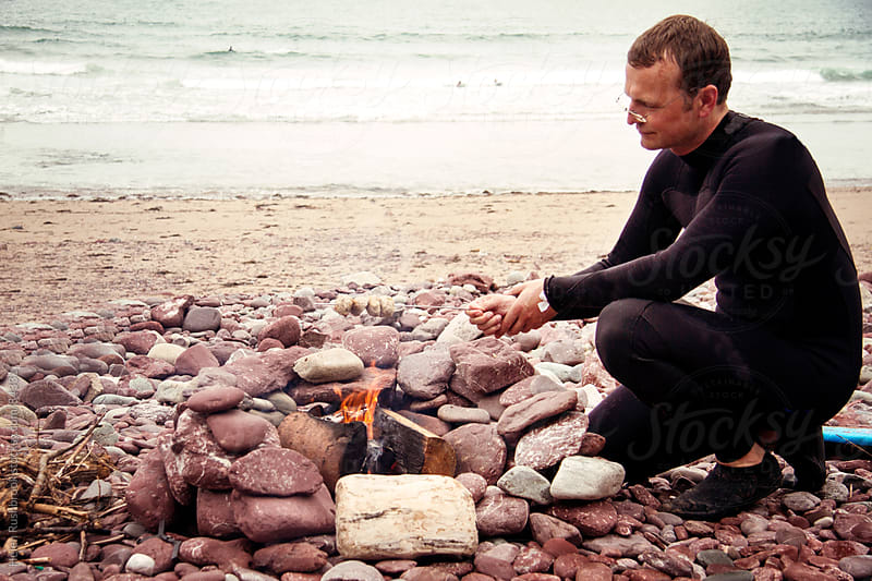 A man in a wetsuit cooking food over a fire on a beach. by Helen Rushbrook for Stocksy United
