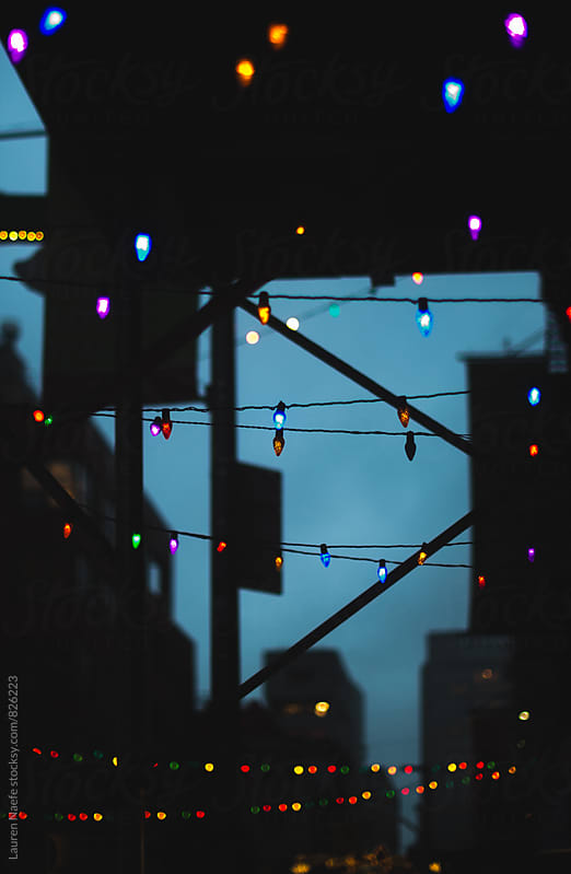 Christmas lights hanging from scaffolding by Lauren Naefe for Stocksy United
