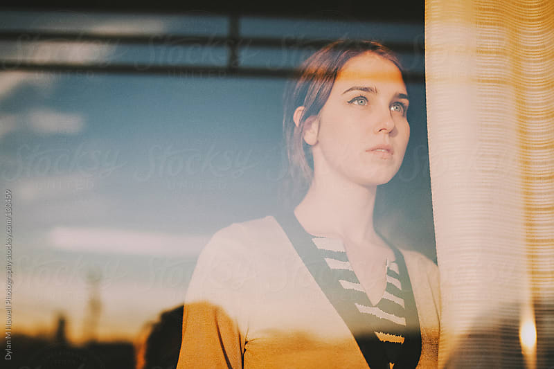 Girl staring out Window by Dylan M Howell Photography for Stocksy United