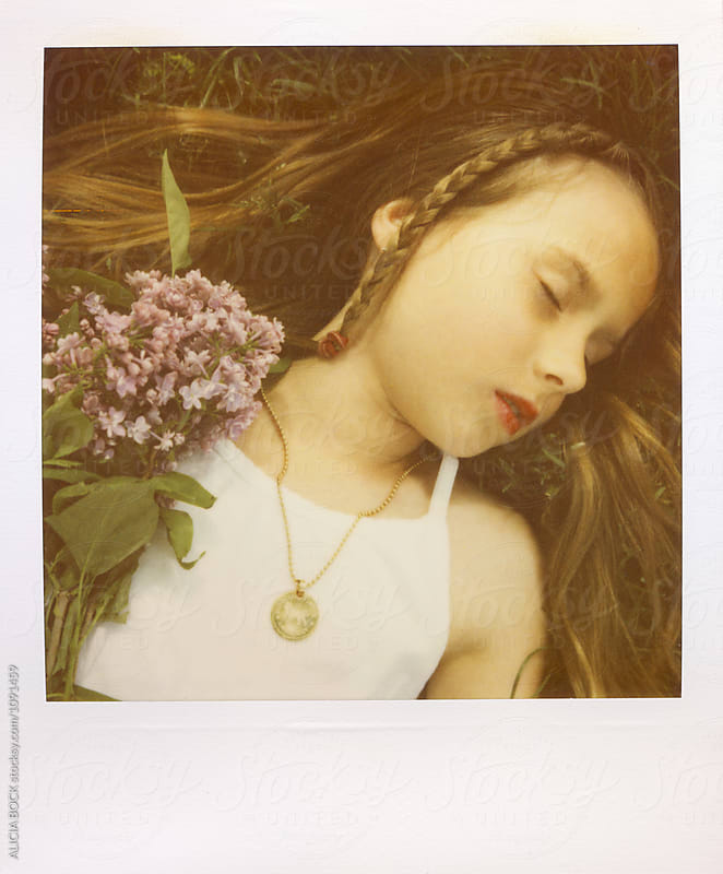 A Girl Resting In The Grass Holding Spring Lilac Flowers Photographed With Expired Polaroid Film by ALICIA BOCK for Stocksy United
