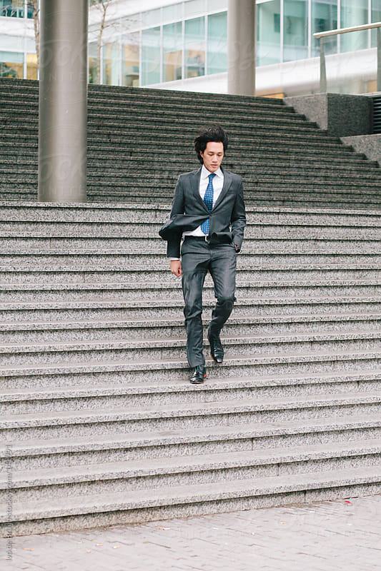 Ambitious asian young businessman running down the stairs by Ivo de Bruijn for Stocksy United