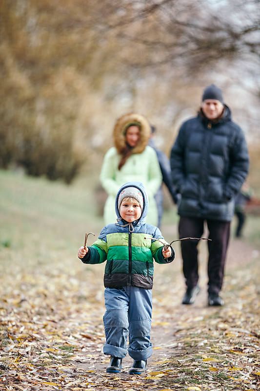 Happy family walking outdoors by Ilya for Stocksy United