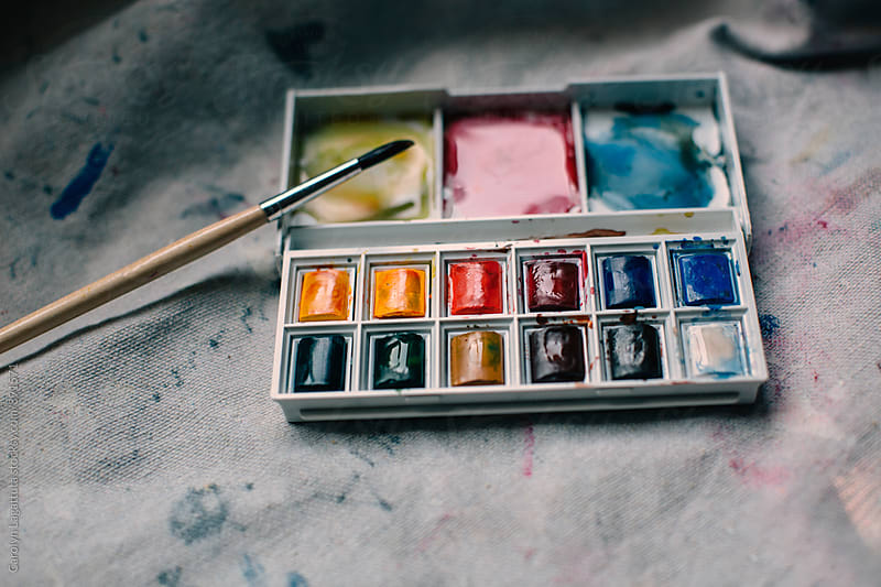 Palette of mini multicolored paints on a canvas by Carolyn Lagattuta for Stocksy United