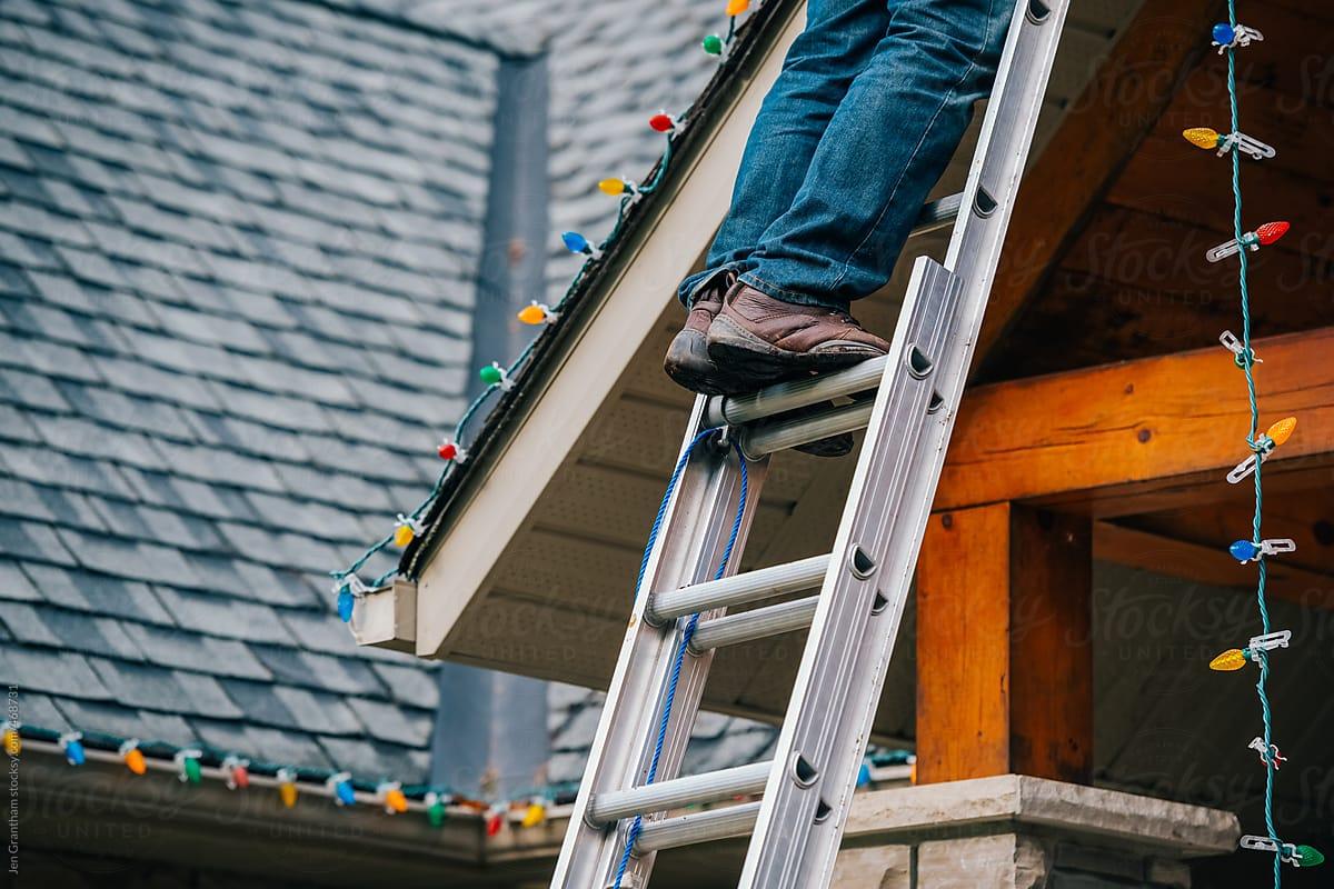 Man Climbing Ladder To Hang Up Christmas Lights By Jen