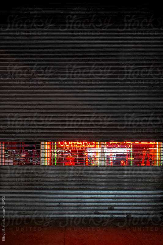 Neon leaks through a security shutter at guitar store by Riley J.B. for Stocksy United