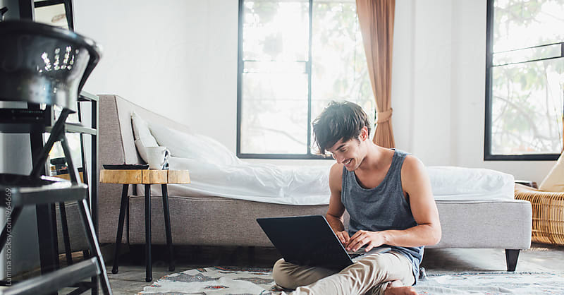 Man Uses His Laptop in a Bedroom by Lumina for Stocksy United