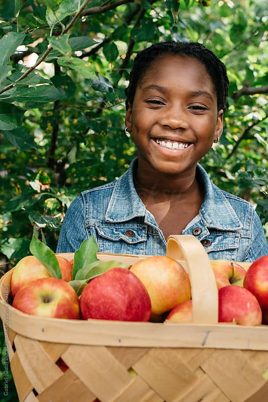 Happy black girl holding apples by Gabriel (Gabi) Bucataru for Stocksy United