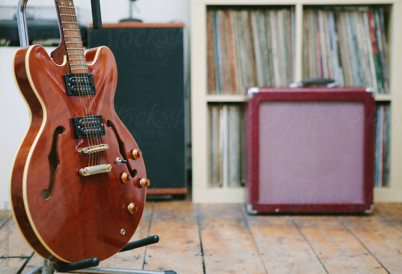 Guitar with amplifier in front of records by kkgas for Stocksy United