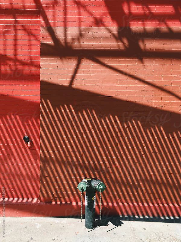 Fire escape shadows on brick wall. Soho. New York City. by Kristin Duvall for Stocksy United