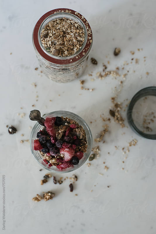 Homemade granola topped with strawberries and blueberries in a glass jar by Daring Wanderer for Stocksy United