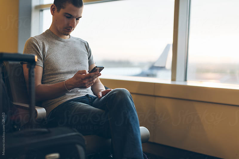 Man Waiting for His Flight and Checking Phone by Mosuno for Stocksy United