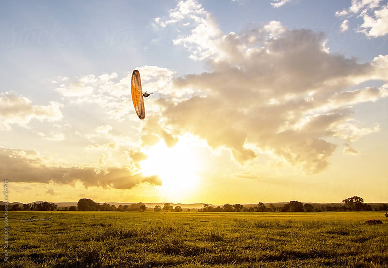 An adventurous paraglider pilot flying close to the ground with the sun setting behind him by Andy Campbell for Stocksy United