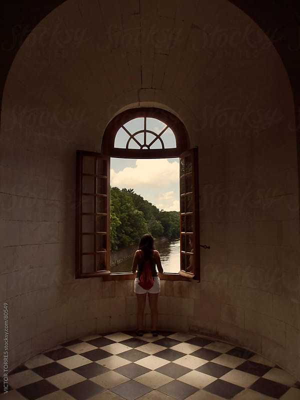 Girl looking through a window of the Chenonceaux Castle by VICTOR TORRES for Stocksy United