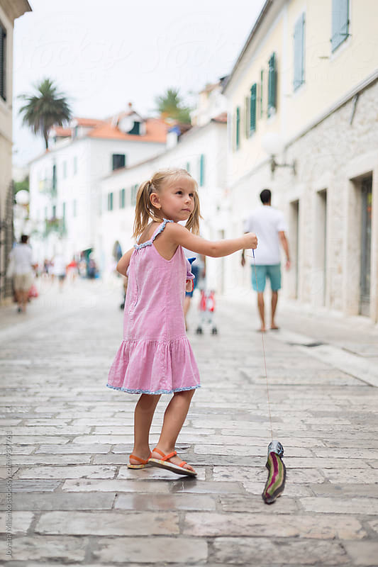 Beautiful little girl walking alone trough the city in Mediterranean in summer by Jovana Milanko for Stocksy United
