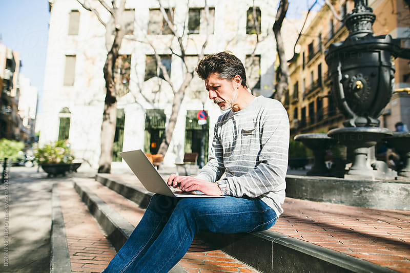Casual mature man working with his laptop on the street. by BONNINSTUDIO for Stocksy United