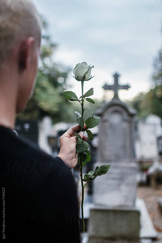 Young blond boy dressed in black with a white rose in front of the grave on cemetery by Igor Madjinca for Stocksy United