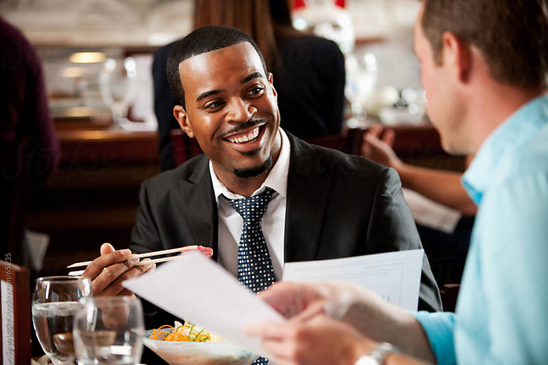 Sushi: Businessman Laughing While Eating and Doing Business by Sean Locke for Stocksy United