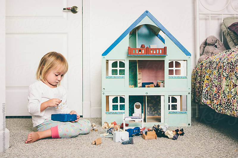 Little Girl Playing With Dollhouse by Stephen Morris for Stocksy United
