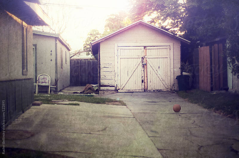 An urban home with a slightly neglected driveway containing a lone dodgeball  by Rachel Bellinsky for Stocksy United