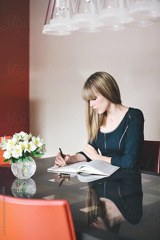 A woman writing by Ania Boniecka for Stocksy United