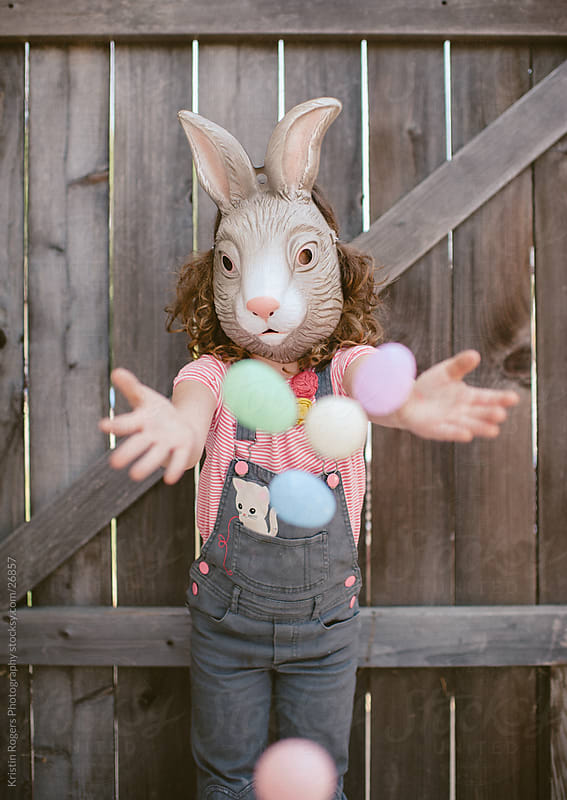Little girl wearing bunny mask playing with Easter Eggs by Kristin Rogers Photography for Stocksy United