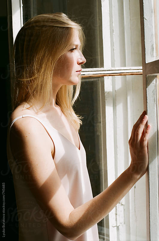 Young woman standing against window by Liubov Burakova for Stocksy United