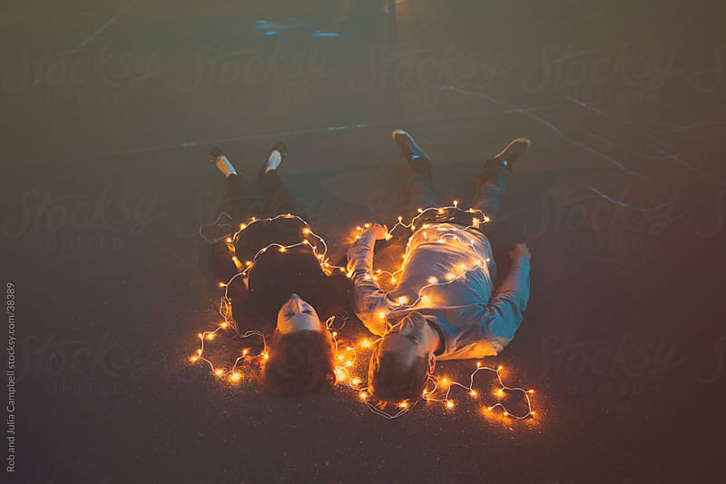 Couple lying down covered in lights by Rob and Julia Campbell for Stocksy United