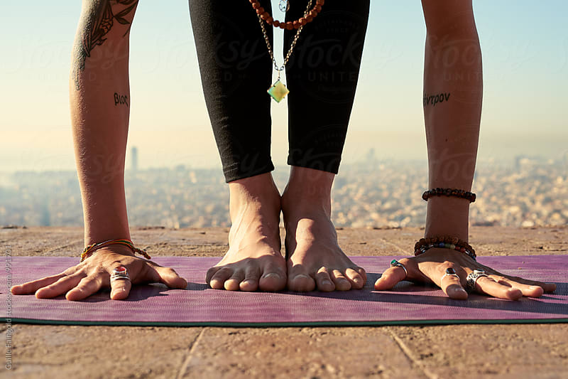 Close-up of barefoot woman preparing for yogic pose by Guille Faingold for Stocksy United