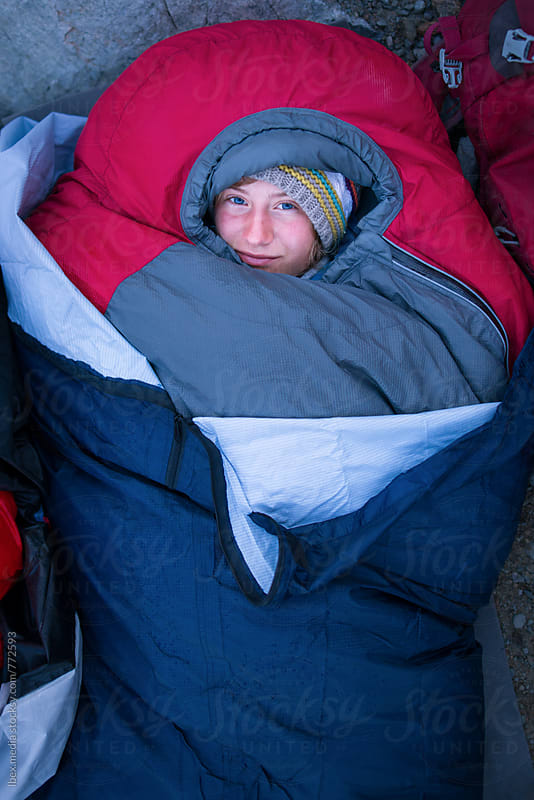 Woman waking up in a down filled sleeping bag outdoor by RG&B Images for Stocksy United