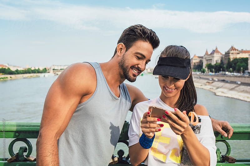 Couple in Fitness Clothes Using a Mobile Phone by Lumina for Stocksy United