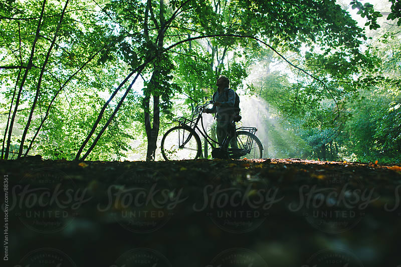 Person standing next to his bicycle in the forest and looks up  by Denni Van Huis for Stocksy United