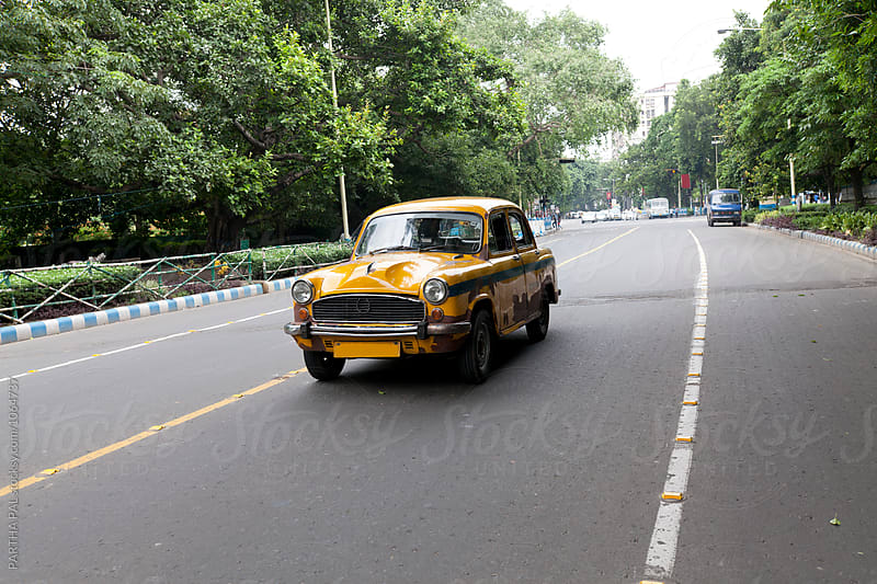 A yellow colored taxi running in a road by PARTHA PAL for Stocksy United