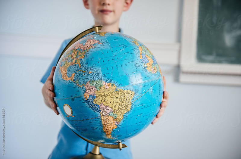 Student in classroom holds a globe by Cara Dolan for Stocksy United