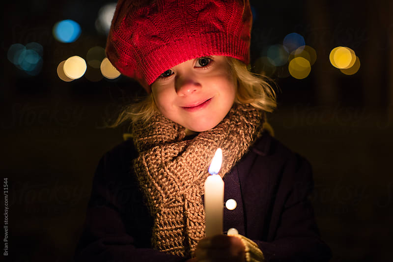 little girl with candle light by Brian Powell for Stocksy United