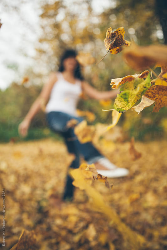 Girl kicking some leafes in autumn park by Robert Kohlhuber for Stocksy United