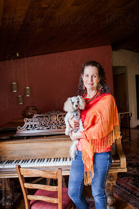Middle age woman holding her pet dog at home by Suprijono Suharjoto for Stocksy United