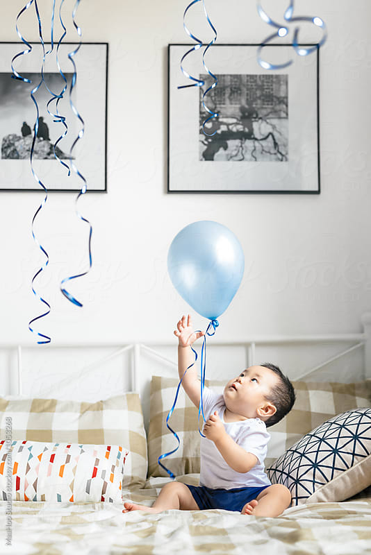 Adorable little boy playing with helium balloons on bed by Maa Hoo for Stocksy United