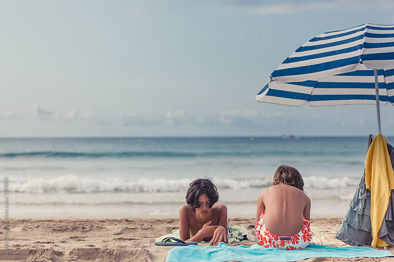 Two boys relaxing on the beach in the summer underneath a parasol by Cindy Prins for Stocksy United