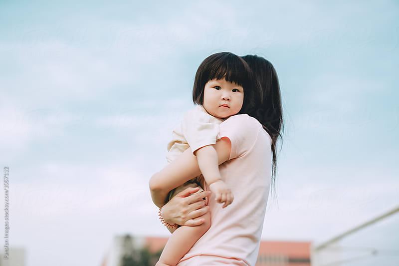 baby girl with her mother outdoor by Xunbin Pan for Stocksy United